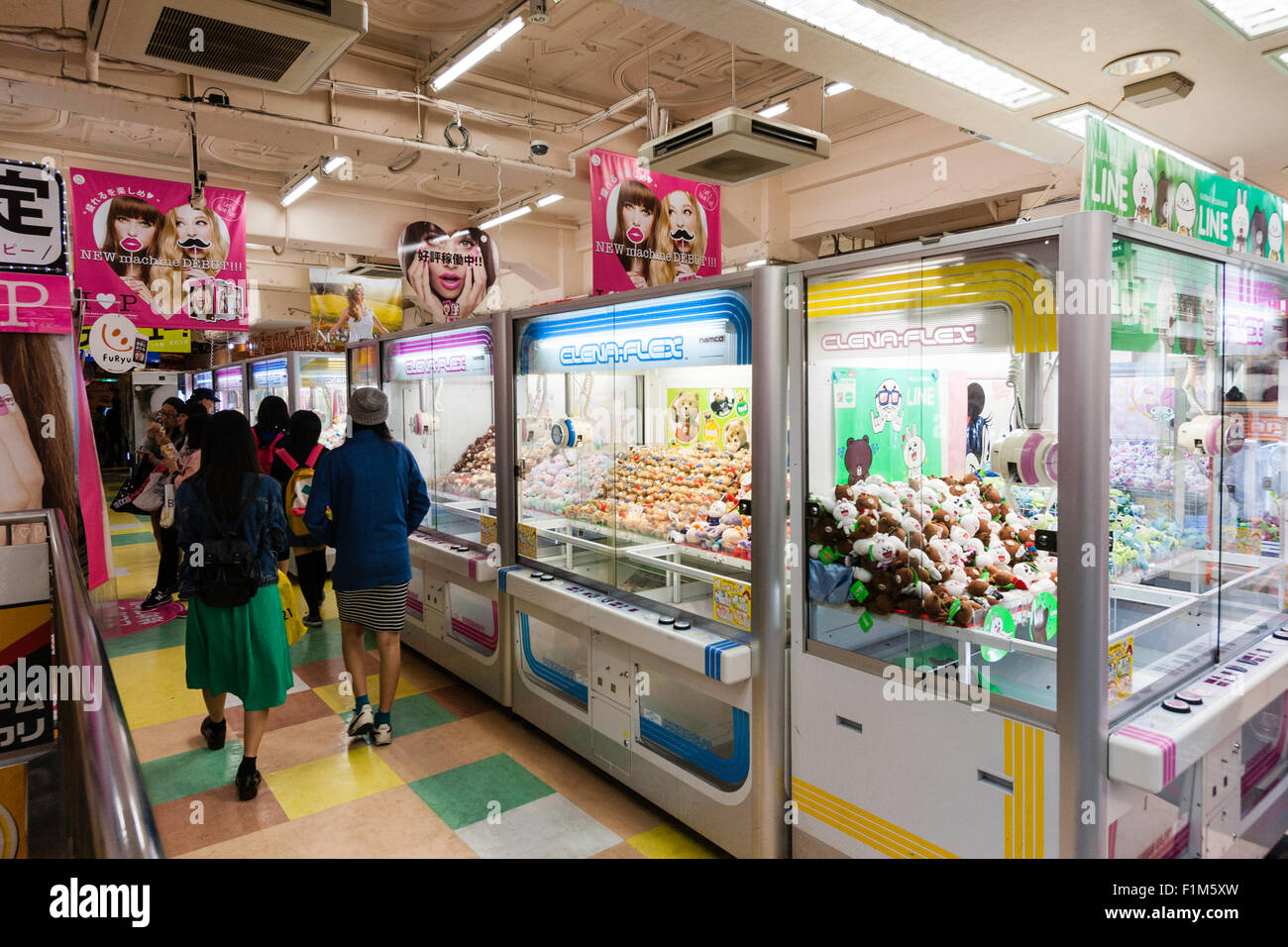 Japan, Osaka, Dotonbori. Interior of games arcade, with rows of game machines and people - Stock Image