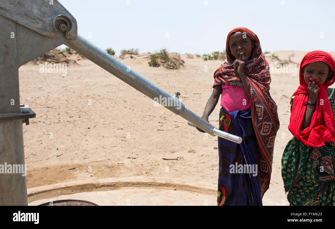 Afar girls pumping water near their village. The hand pump was installed by 'Save The Children' NGO. - Stock Image