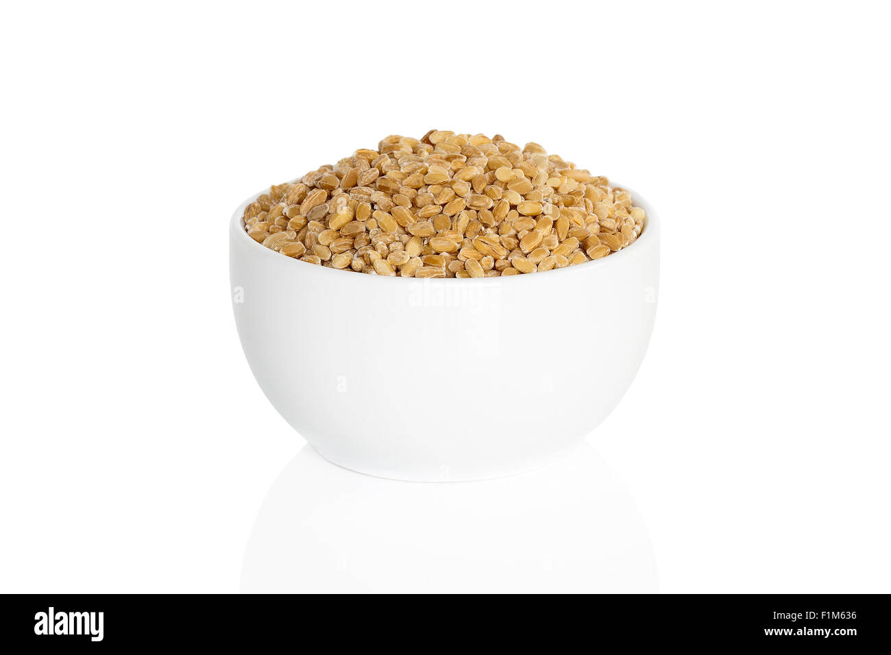 Pearl barley seeds in a cup isolated on a white background - Stock Image