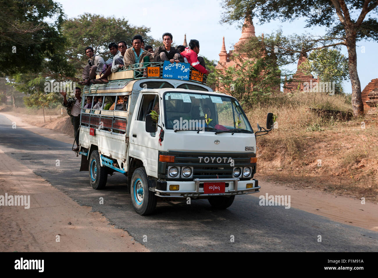 Public transportation, minibus with people in it and on the roof, driving on the road, in Bagan, Mandalay region, - Stock Image