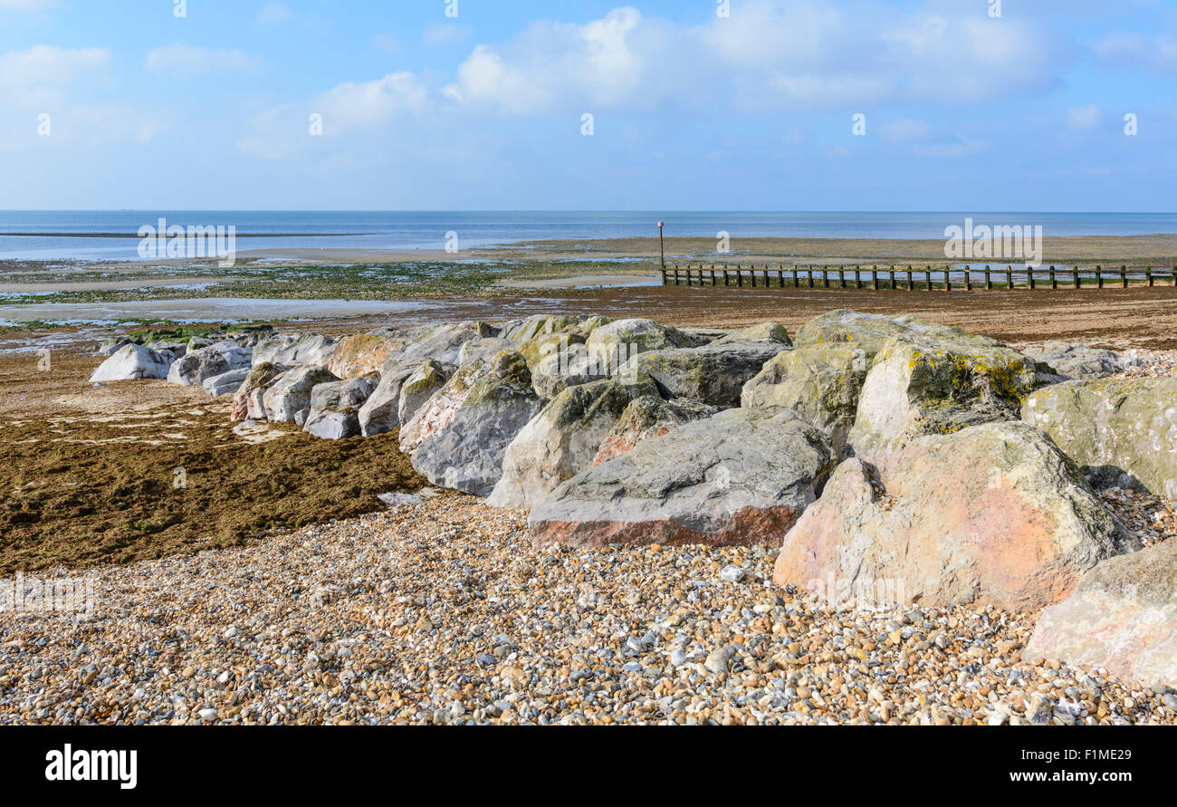 Large rocks on a shingle beach at the seaside. - Stock Image