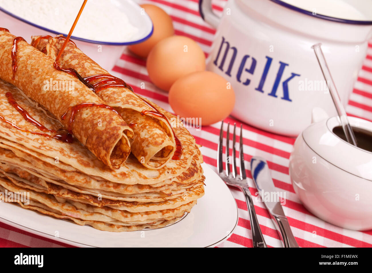 A stack of Dutch 'pannenkoeken met stroop' or pancakes with syrup. - Stock Image
