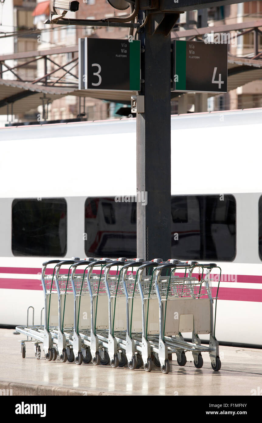 Lugage trolleys in a railway station with train - Stock Image