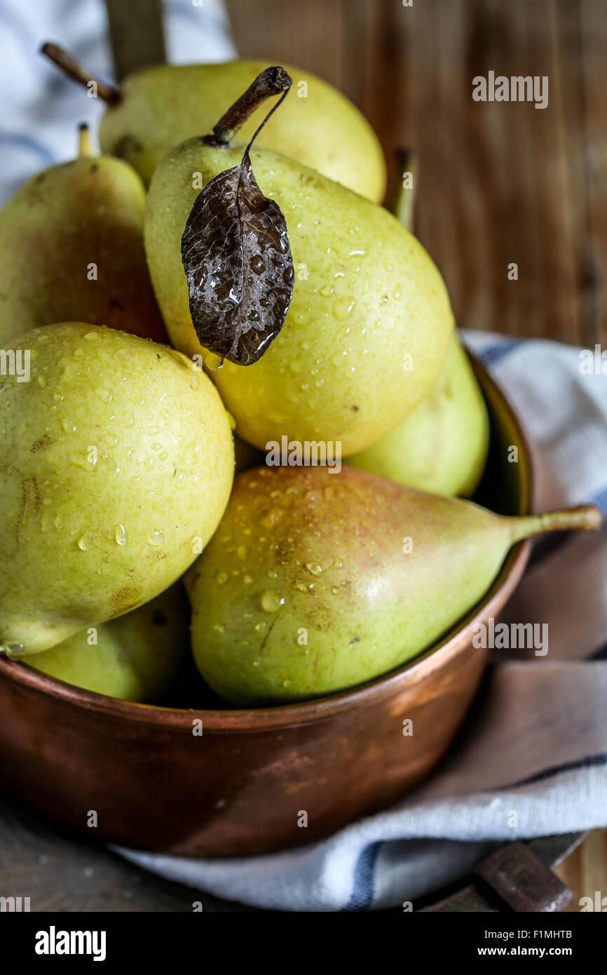 Fresh pears on a copper casserole. - Stock Image