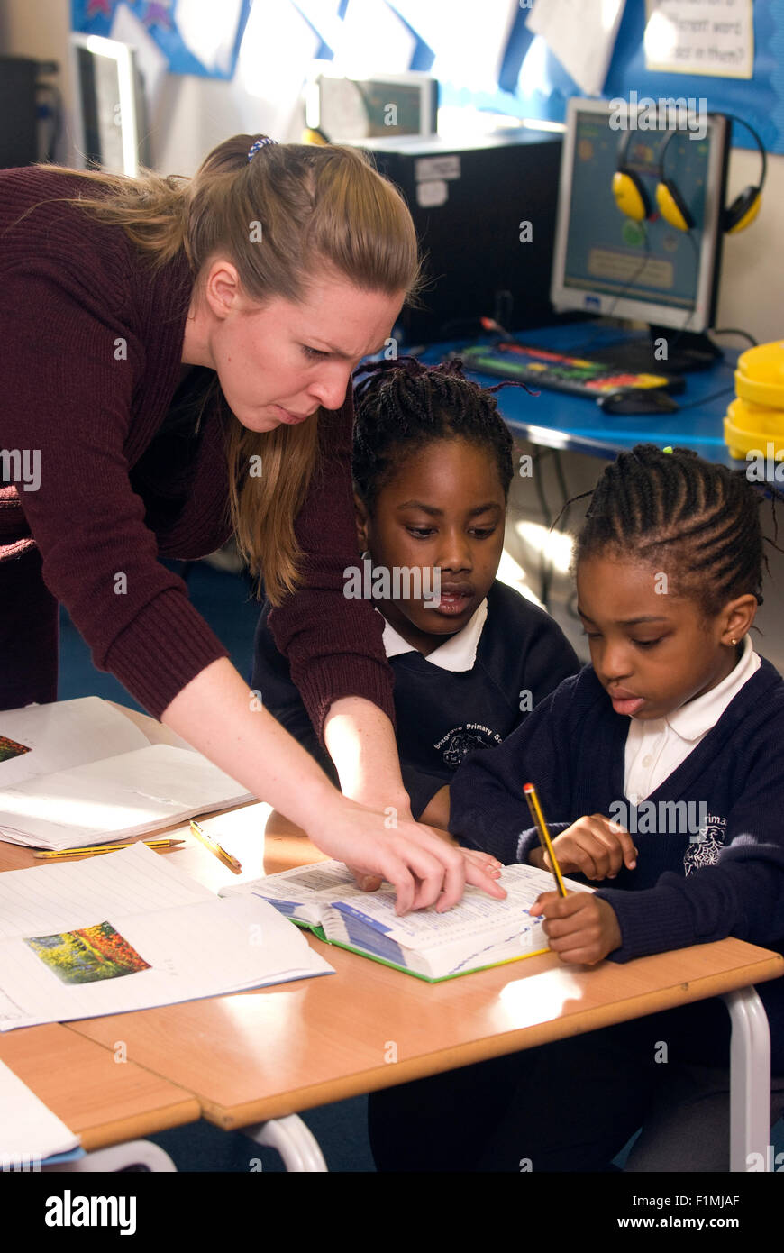 Female primary school teacher assisting pupil's in classroom, London, UK. - Stock Image