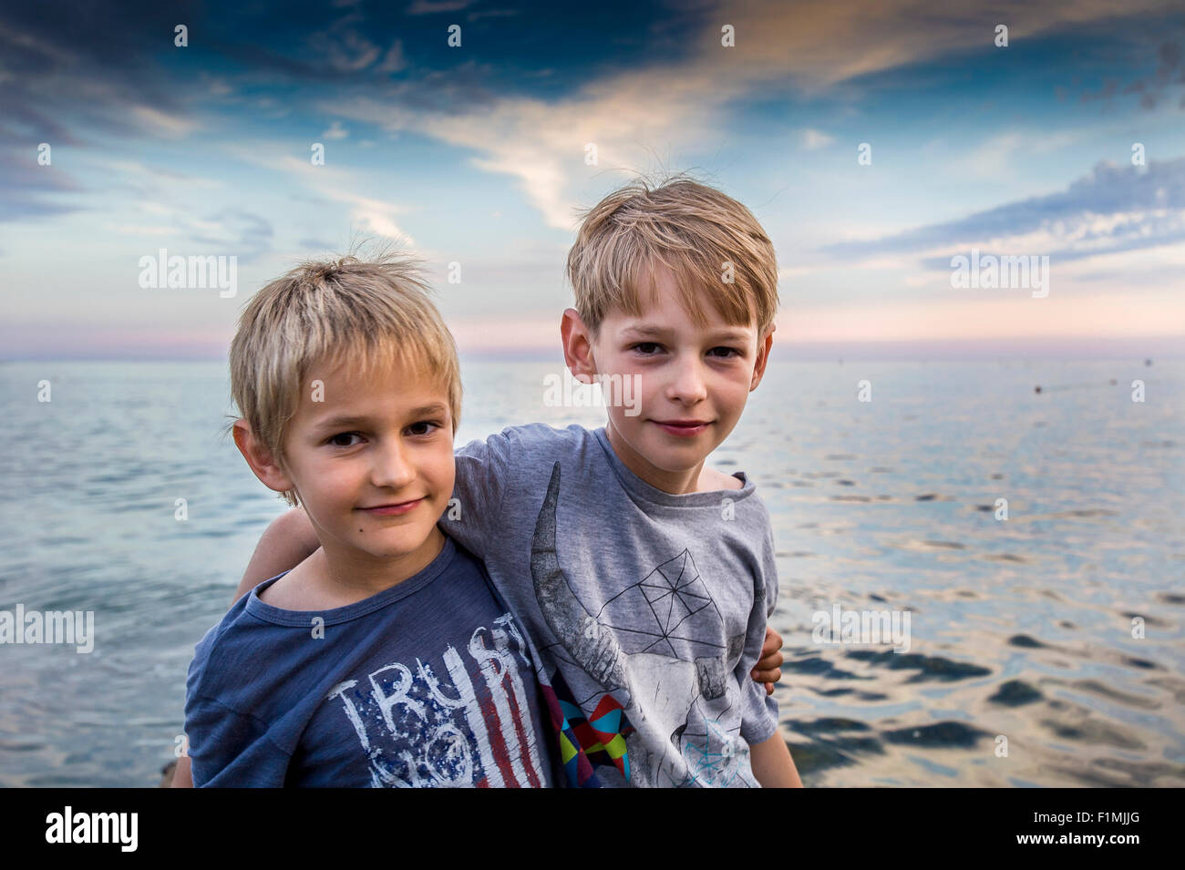 two young brothers in embrace at seacoast - Stock Image