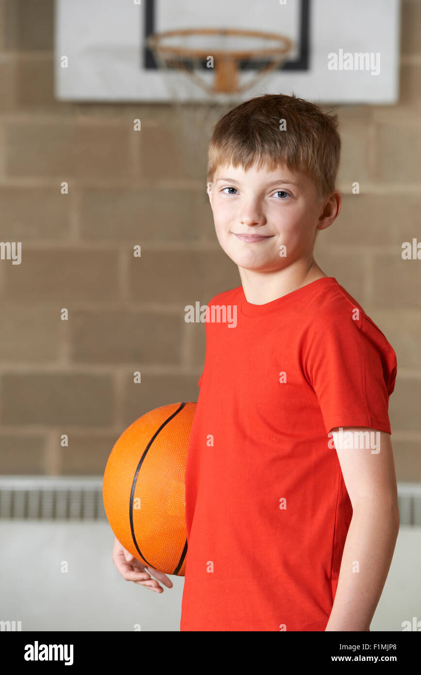 Portrait Of Boy Holding Basketball In School Gym Stock Photo