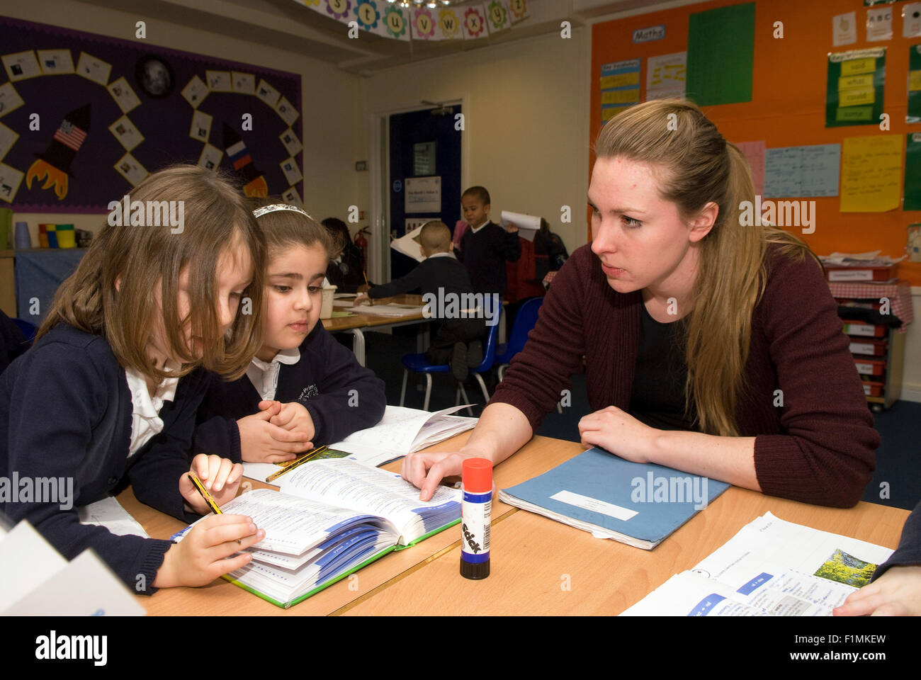 Primary school teacher helping pupil's in class, London, UK. - Stock Image