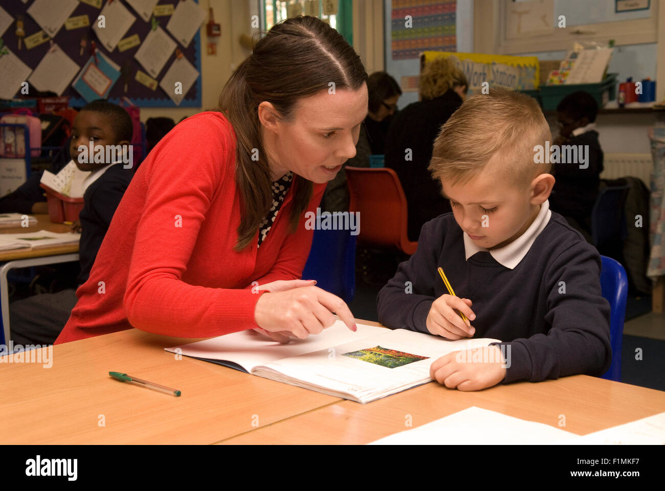primary school teacher assisting pupil in classroom london uk