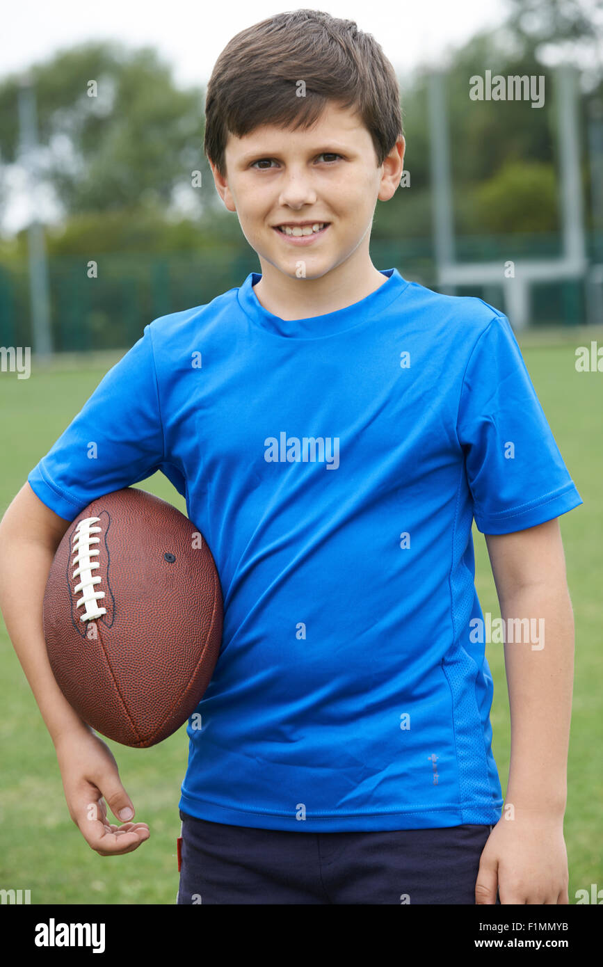 Portrait Of Boy Holding Ball On School Football Pitch - Stock Image