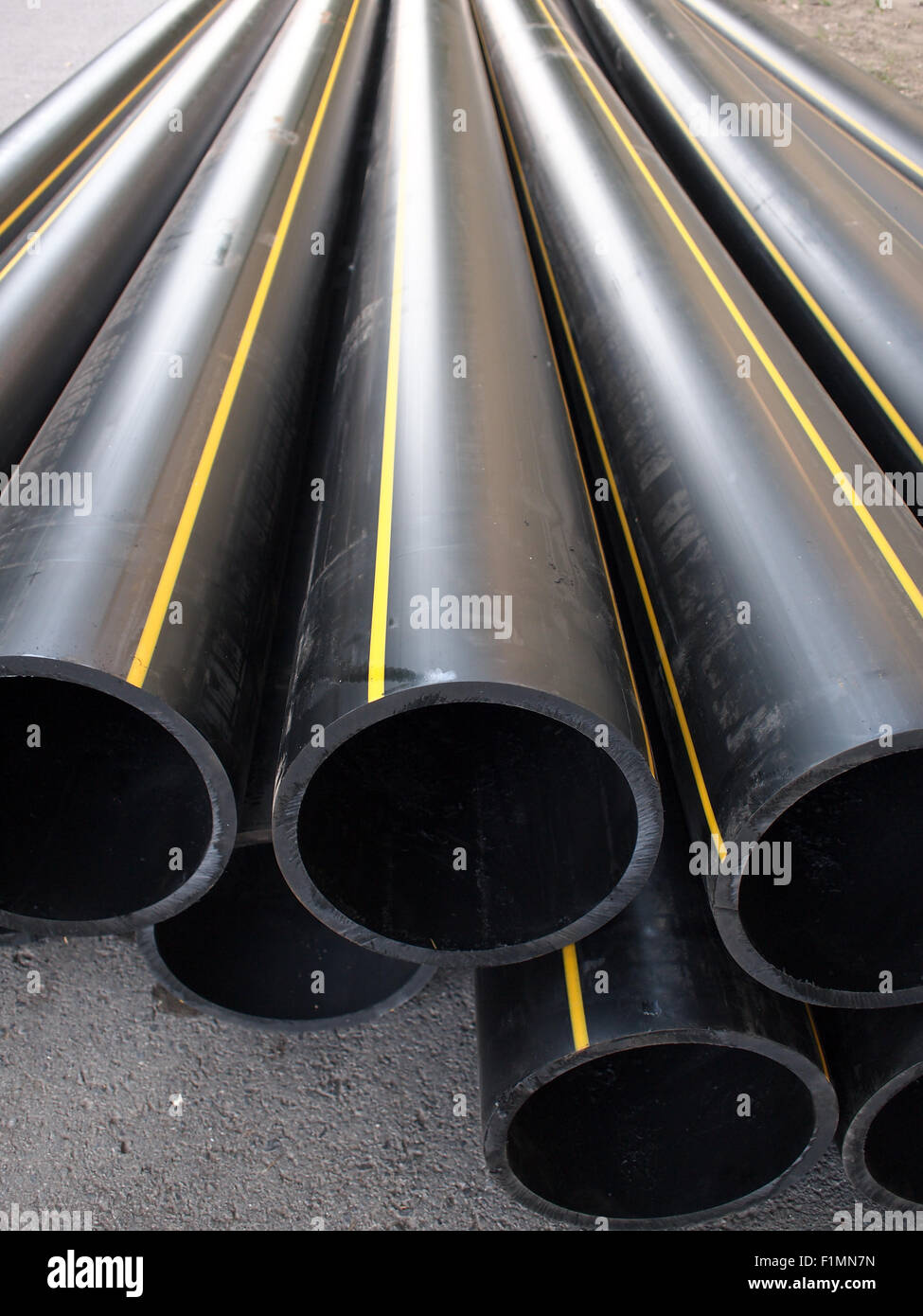 Black plastic PVC pipe lying on the street, a great bunch. Selective focus with shallow depth of field. - Stock Image