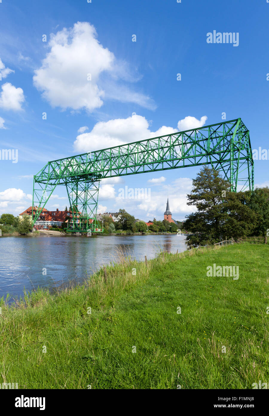 Historic transporter bridge across the Oste river and Osten village with baroque church St.-Petri - Stock Image