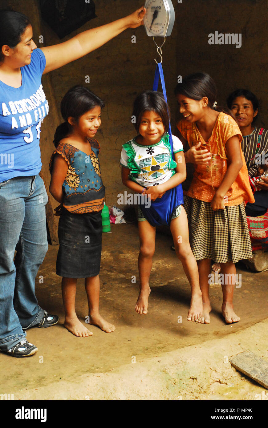 Guatemala, la Democratia, small girl (Lorena Lopez Mendez 4 years) being weighted with sisters watching (Anabela - Stock Image