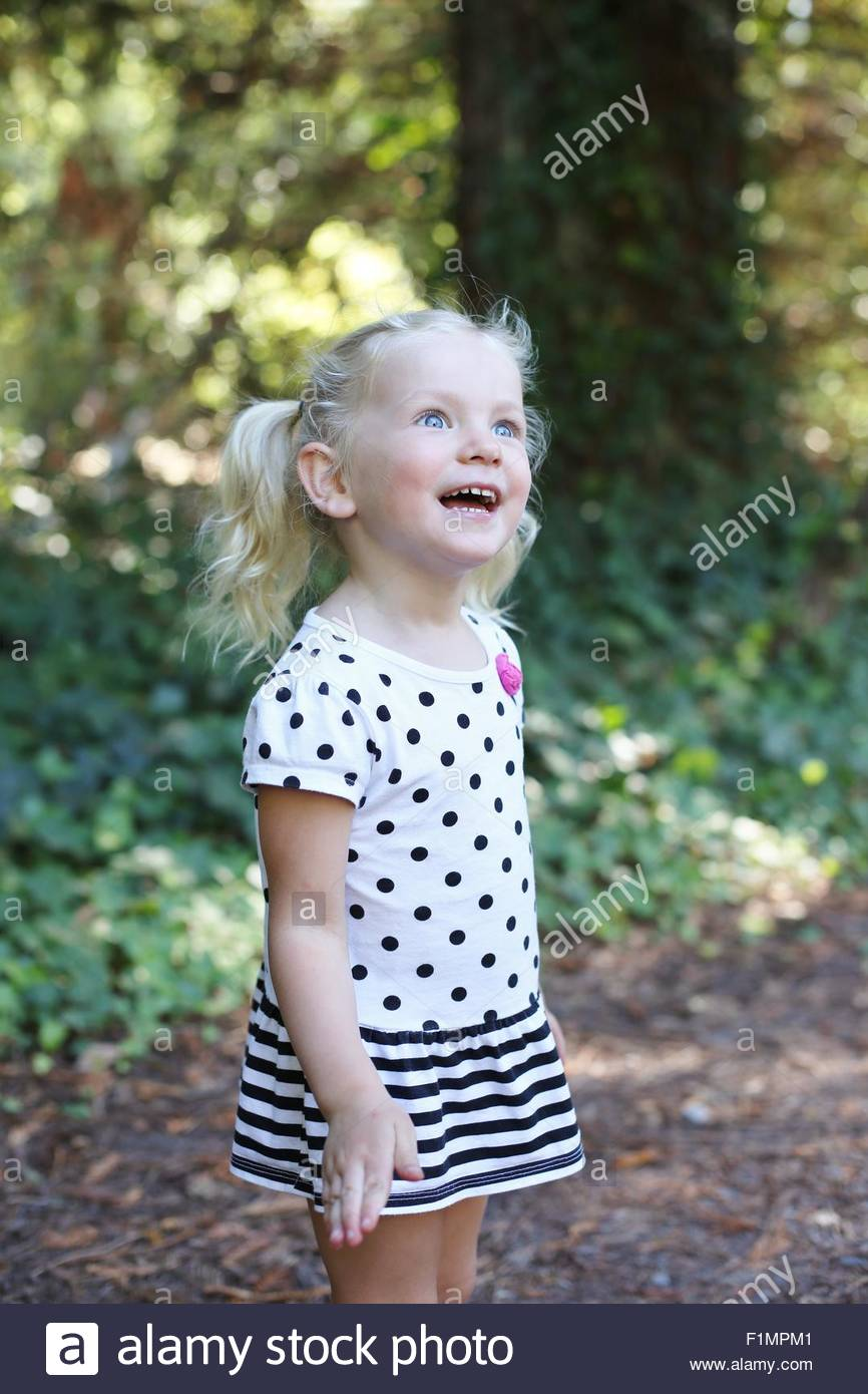 A little girl looking excited and surprised. - Stock Image