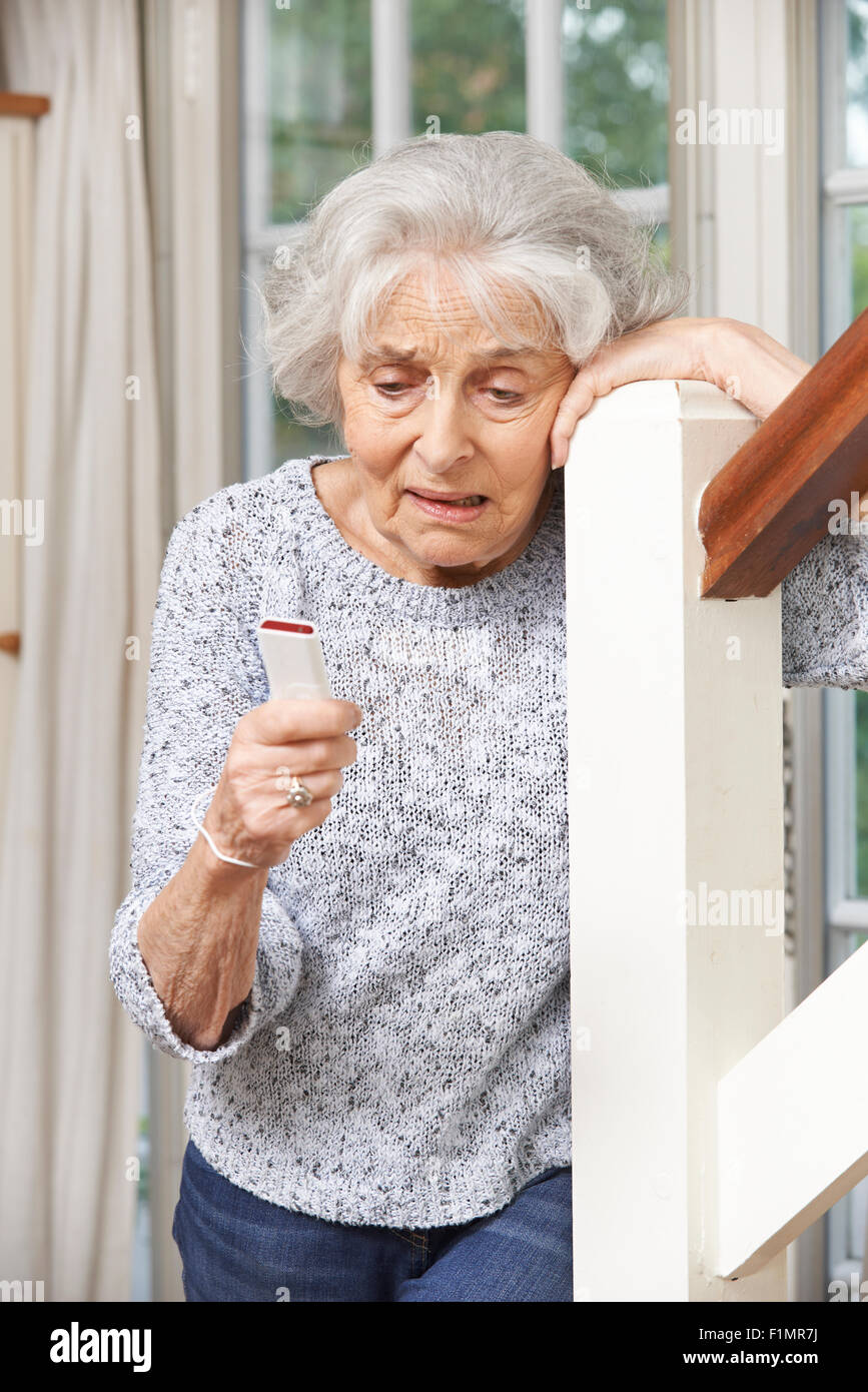 Unwell Senior Woman Using Personal Alarm At Home - Stock Image