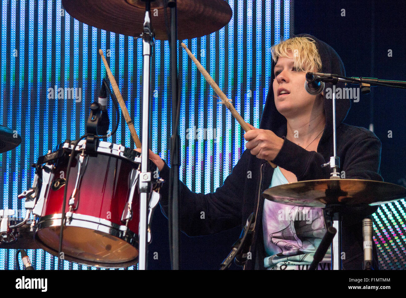 Cat Myers of Honeyblood drumming at Victorious Festival 2015 with hood up. - Stock Image