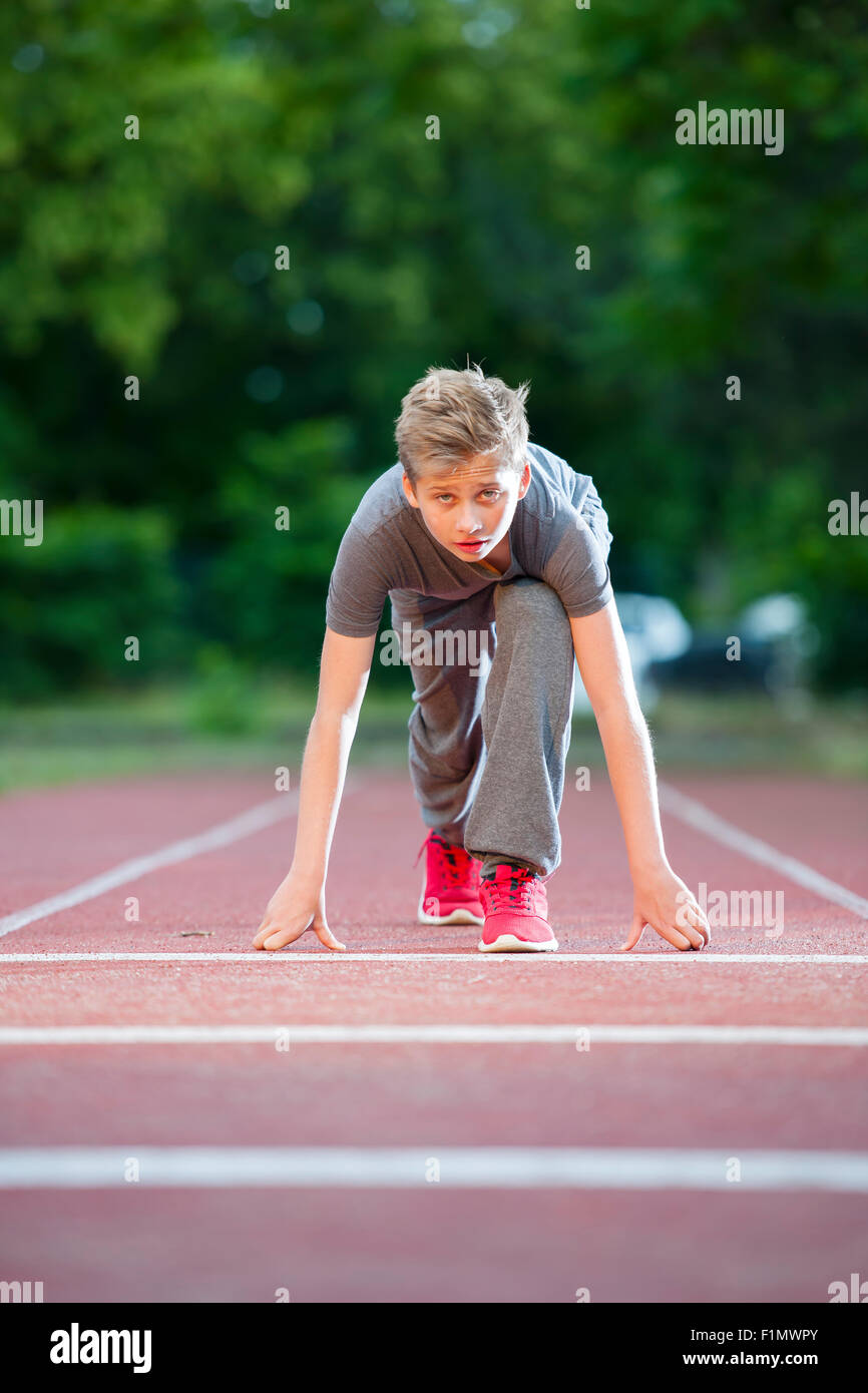 deep frontal full-body view looking a young male teenagers in Tiefstart position on a tartan track in the camera - Stock Image
