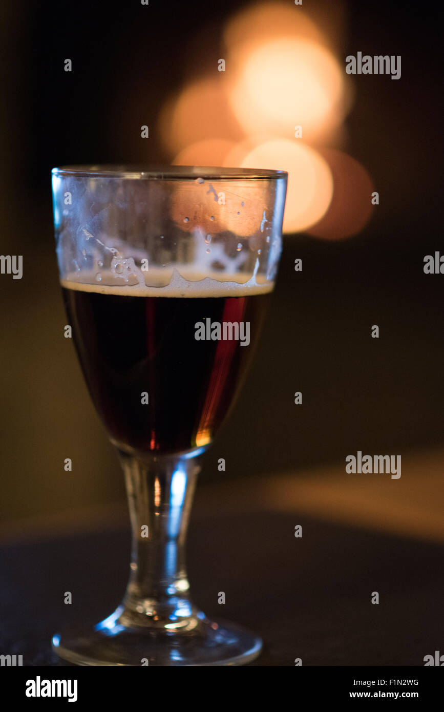 Small single glass of dark beer on a table infront of a cosy real fire on a winter's afternoon in England - Stock Image