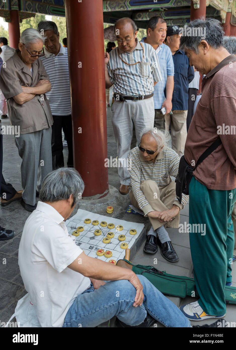 Elderly men watch others playing Chinese checkers at a park near the Temple of Heaven, Beijing Stock Photo