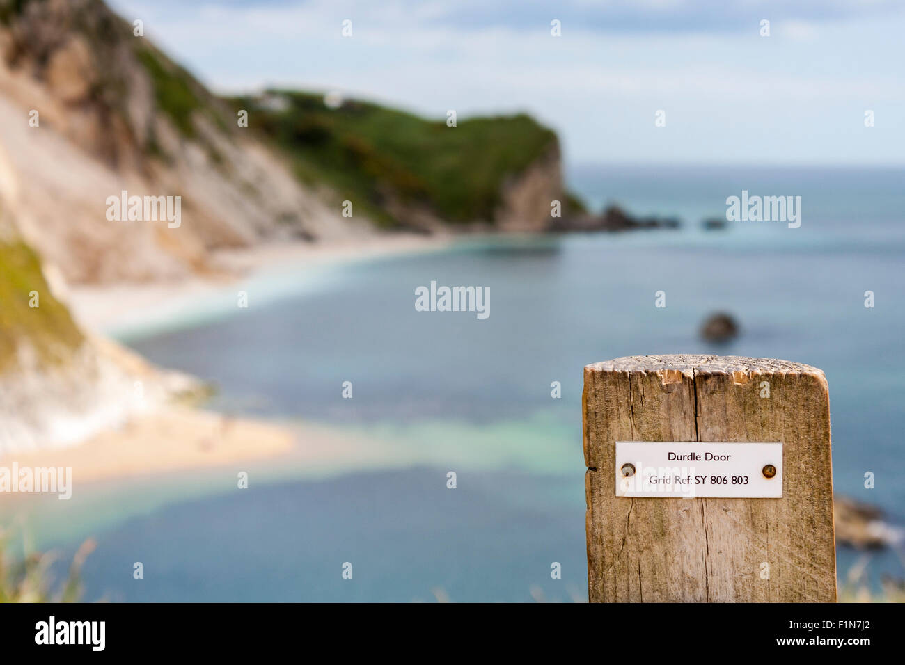 Grid reference on fence post giving map location for walkers at Durdle Door in Dorset. In the out of focus background - Stock Image