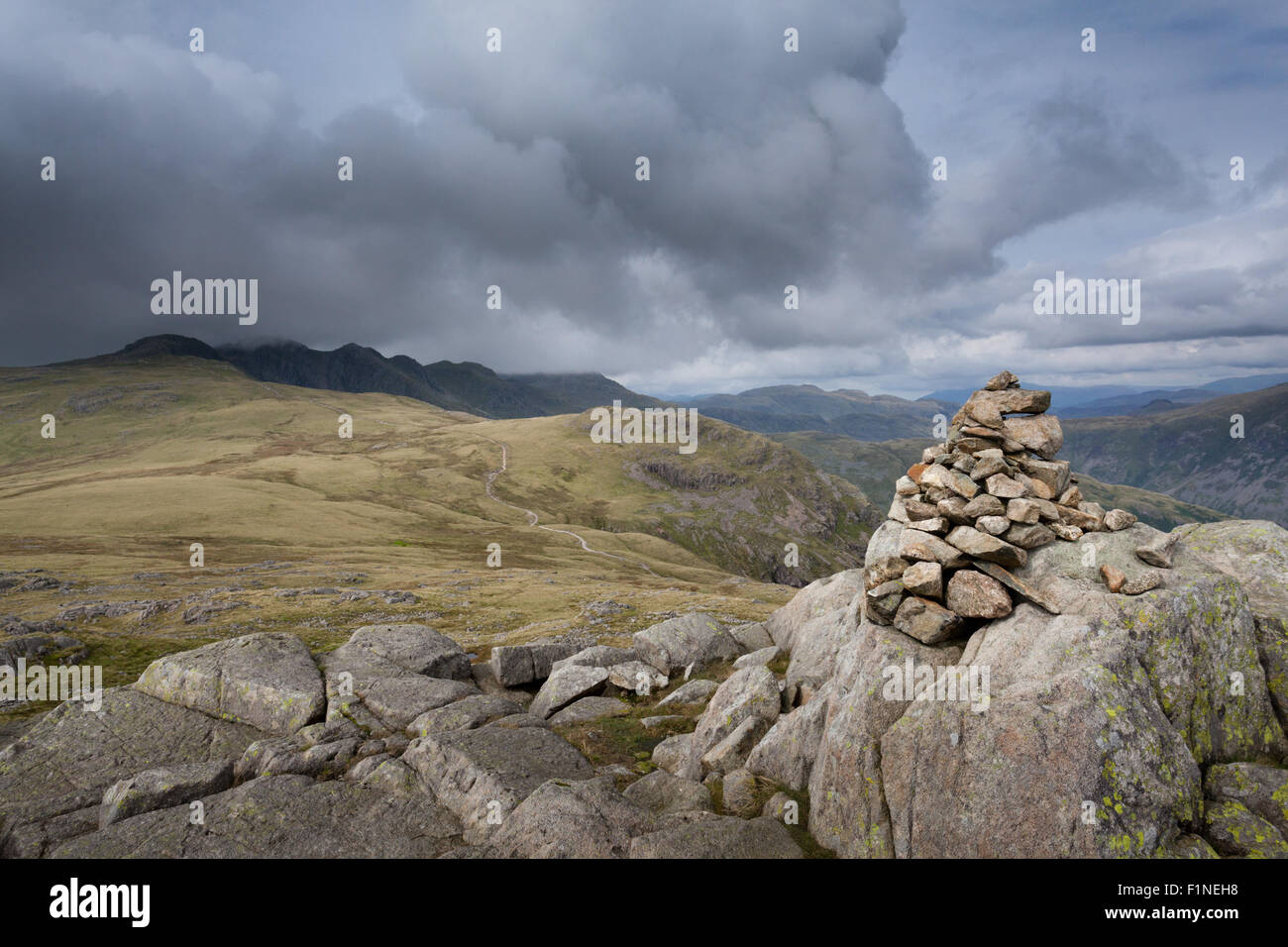 Cold Pike summit cairn looking across to the Crinkle Crags under a moody sky, in the English Lake District - Stock Image