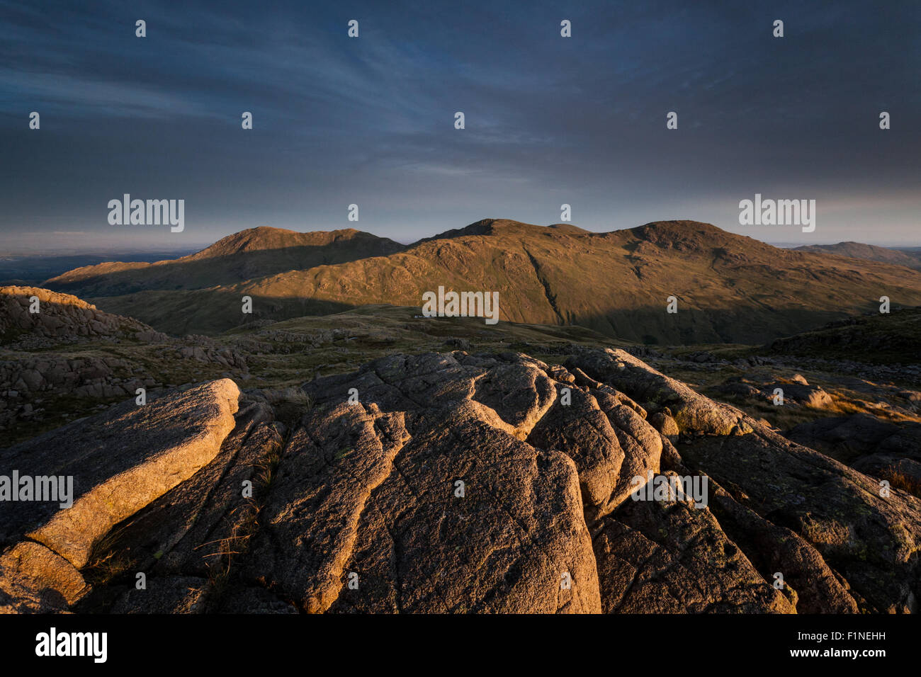 Cold Pike crags view across to Wetherlam, English Lake District, in the evening light, at sunset - Stock Image