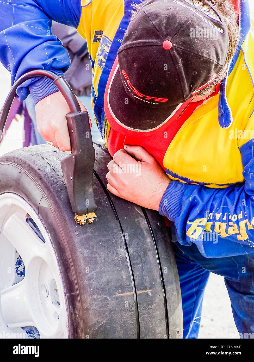 A mechanic uses a heat gun to re cut treads to add tread to a slick worn tyre - Stock Image