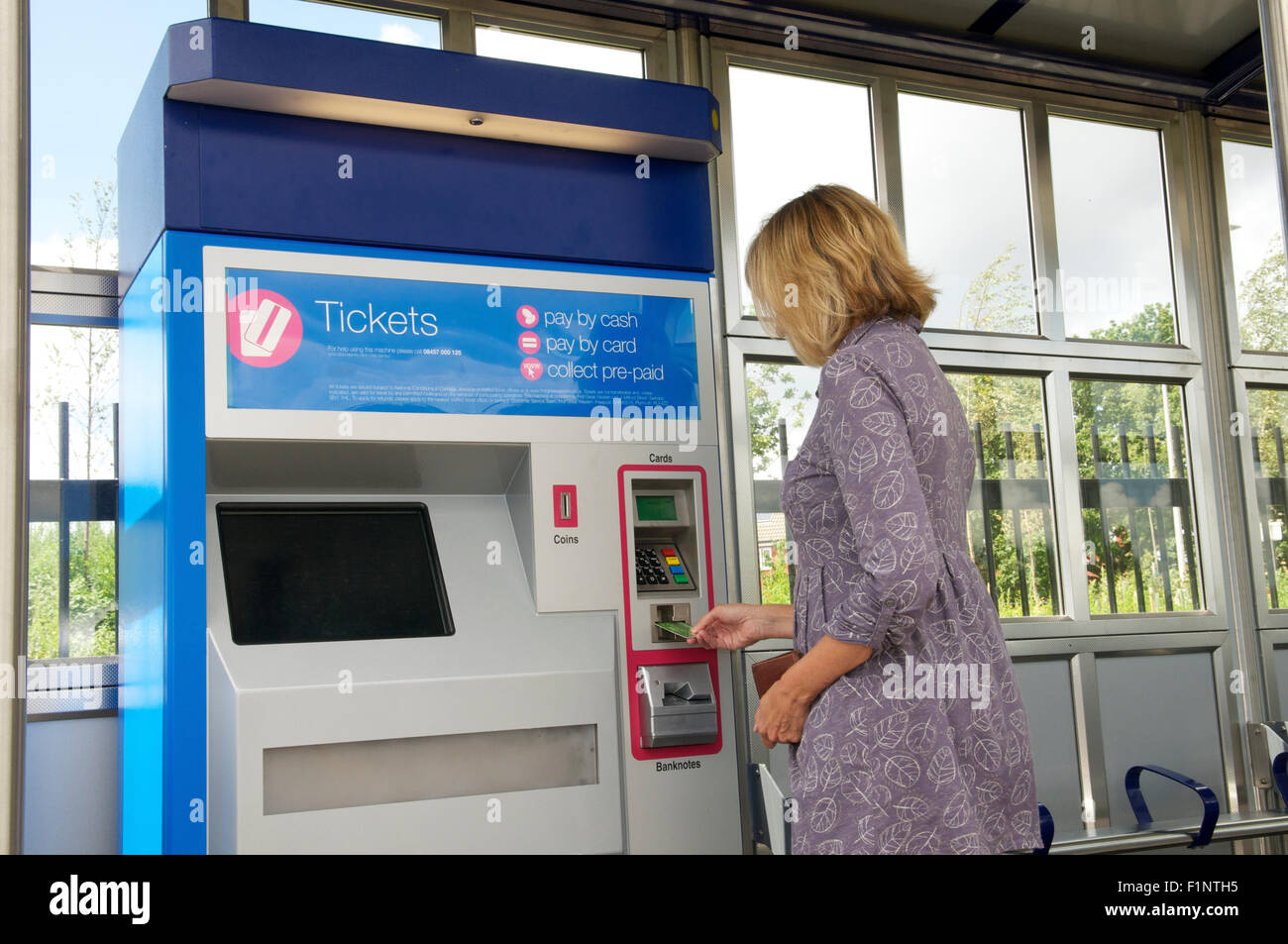 Woman buying rail ticket from a ticket machine at a station, UK - Stock Image