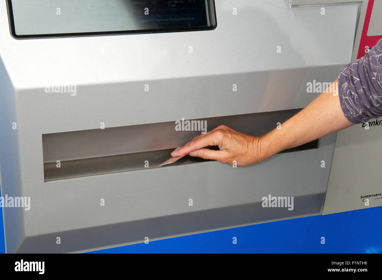 Taking rail ticket from a machine - Stock Image
