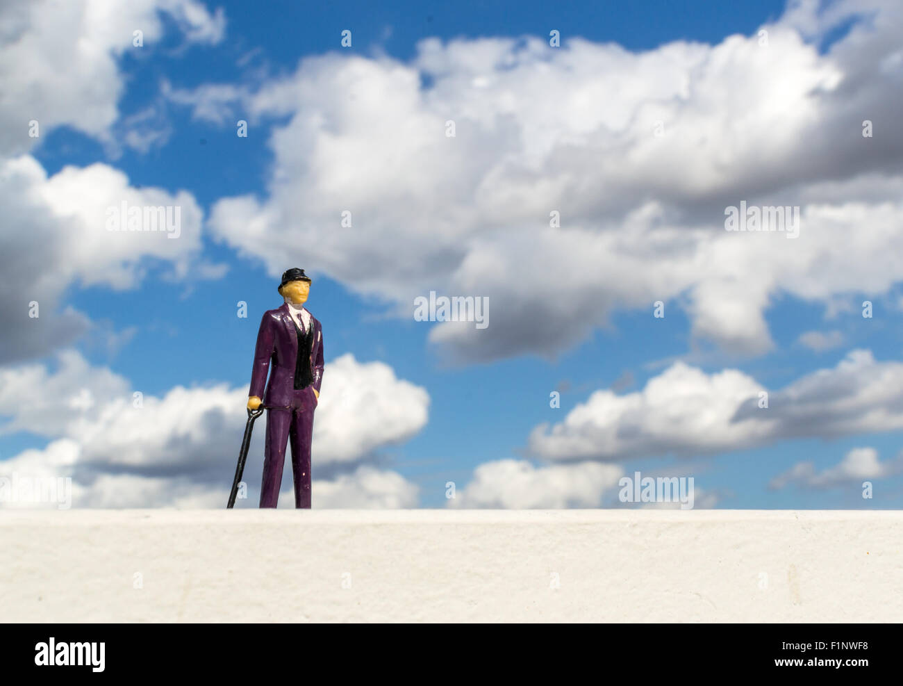 Single business man miniature toy wearing a formal purple suit and holding a walking stick against a cloudy blue - Stock Image