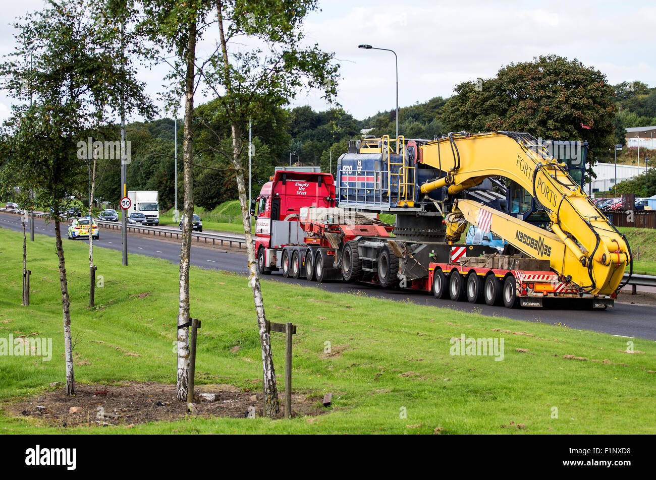 A Police Scotland police car escorting a Forth Ports Crane on the Kingsway West Dual Carriageway in Dundee, UK Stock Photo