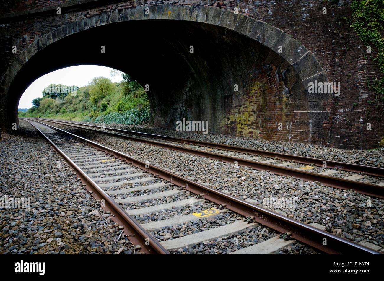 Railway rail tracks under bridge - Stock Image