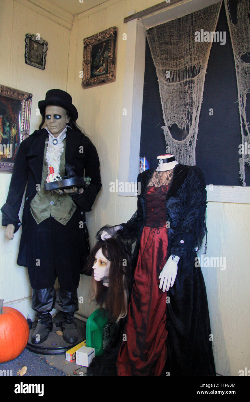 A Halloween monster in suit and top hat stands next to a headless woman holding her head in hand & A Halloween monster in suit and top hat stands next to a headless ...