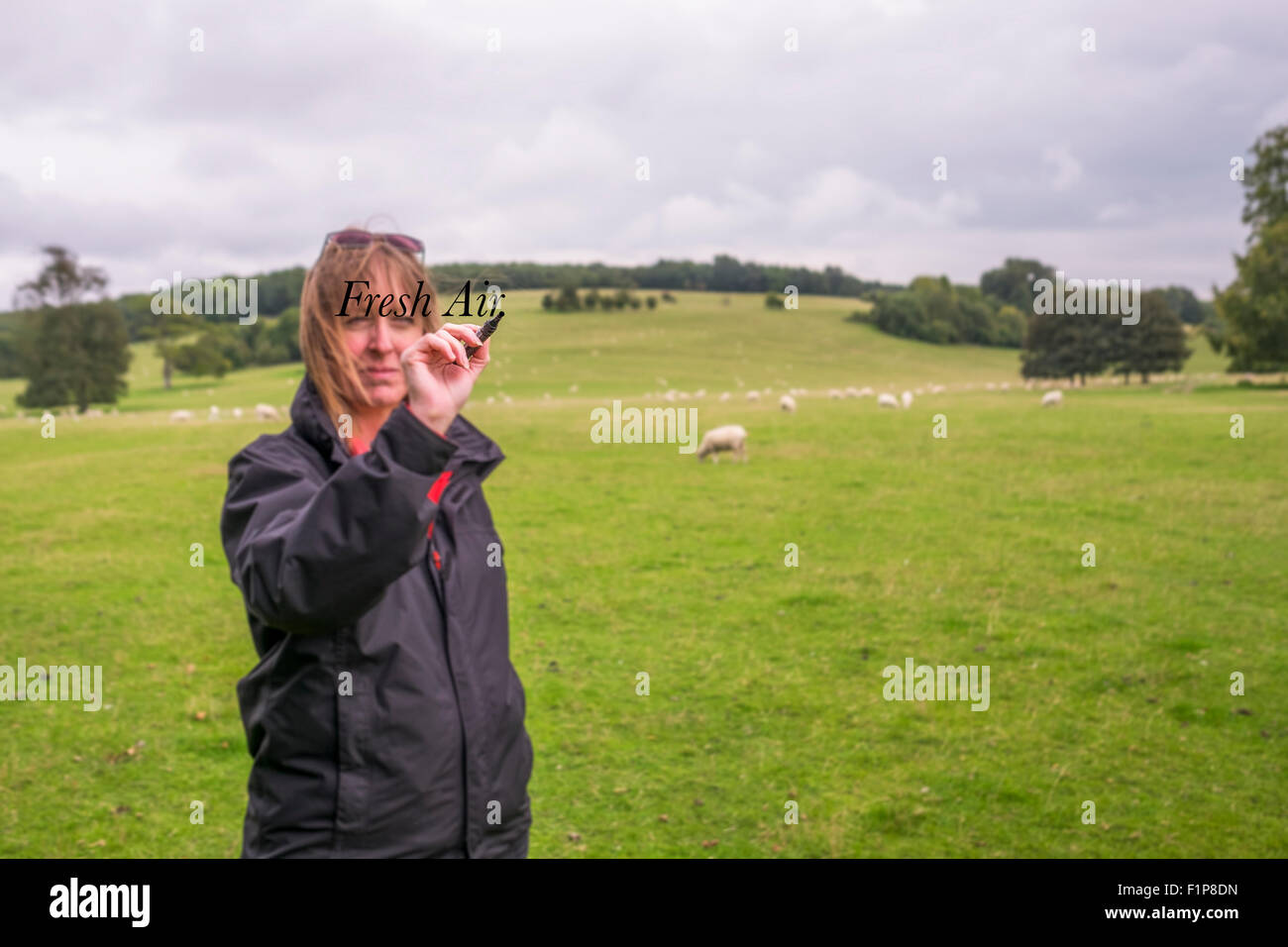 A middle aged woman standing outside in the fresh air of the southdowns national park writing on the words on a - Stock Image
