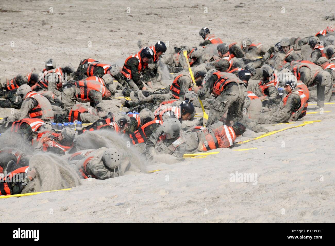 US Navy SEAL candidates cover themselves in sand during surf passage on Naval Amphibious Base Coronado September - Stock Image