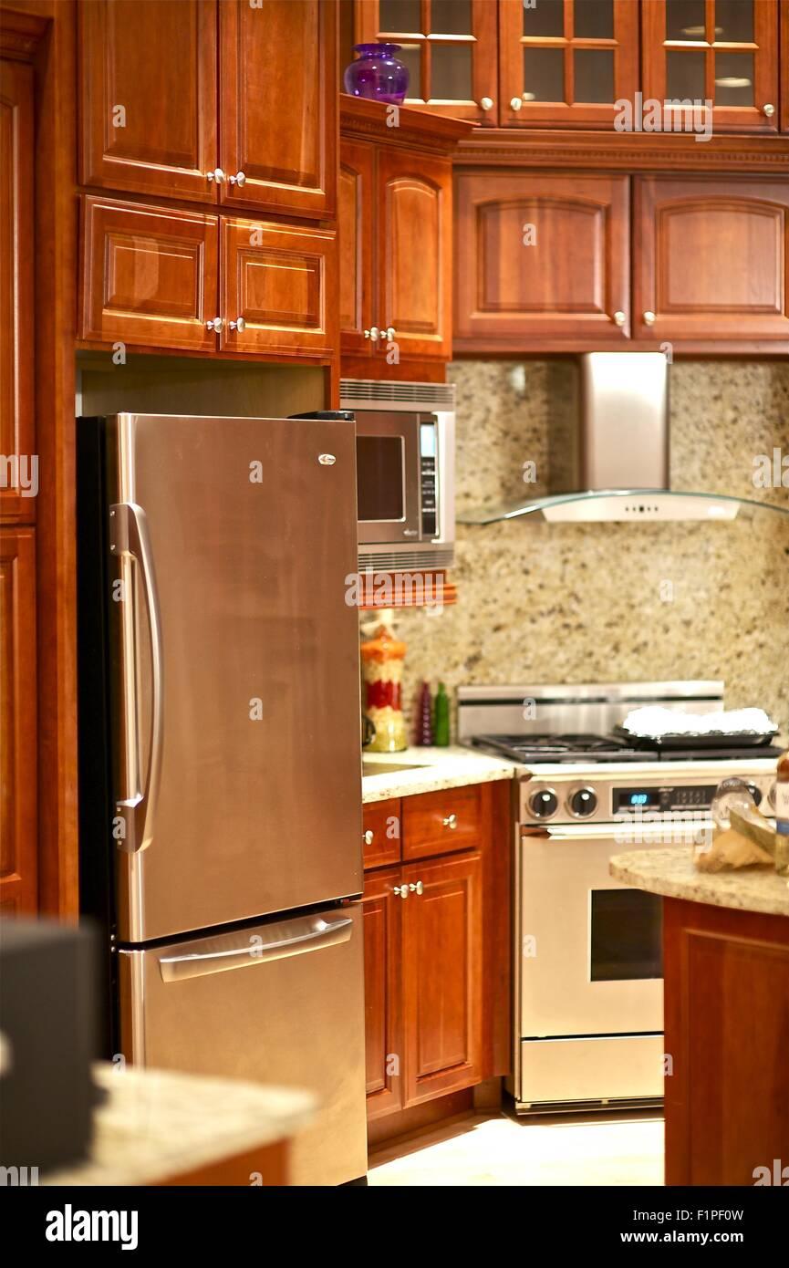 Elegant Luxury Dark Wood Kitchen with Polished Metal Appliance. Luxury Home Interiors. - Stock Image