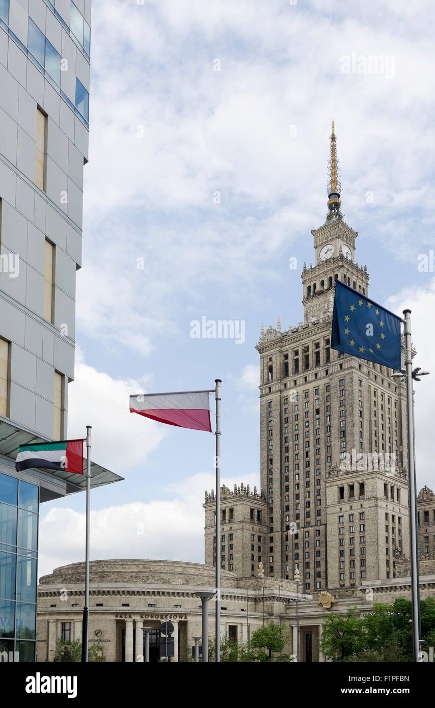 Palace of Culture - Palac Kultury architecture with 3 flags Polish, European Union and United Arab Emirates in Warsaw, Stock Photo