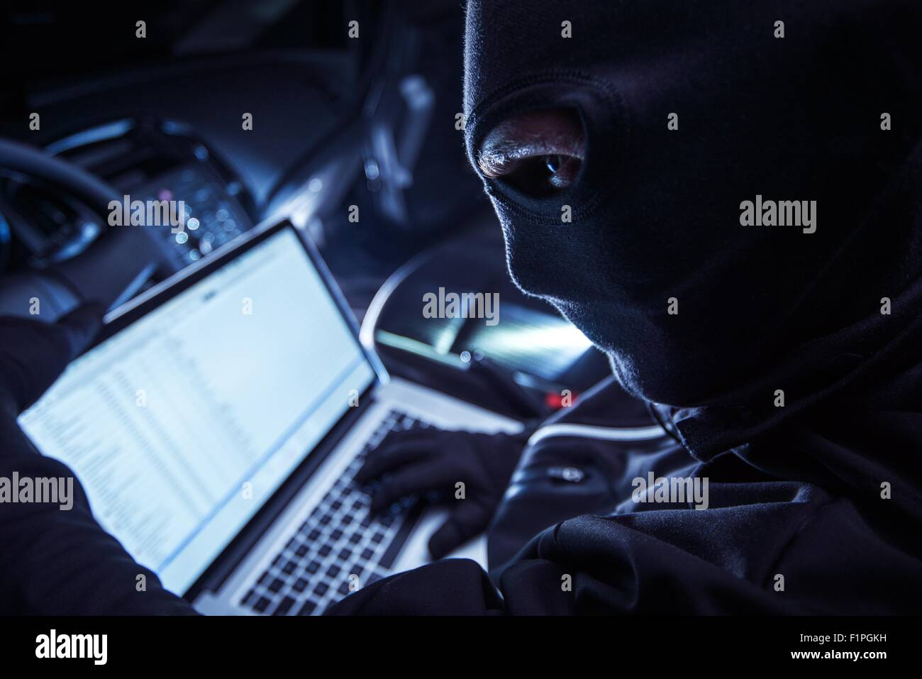 Hacker Inside the Car. Car Robber Hacking Vehicle From Inside Using His Laptop. Hacking On board Vehicle Computer. - Stock Image