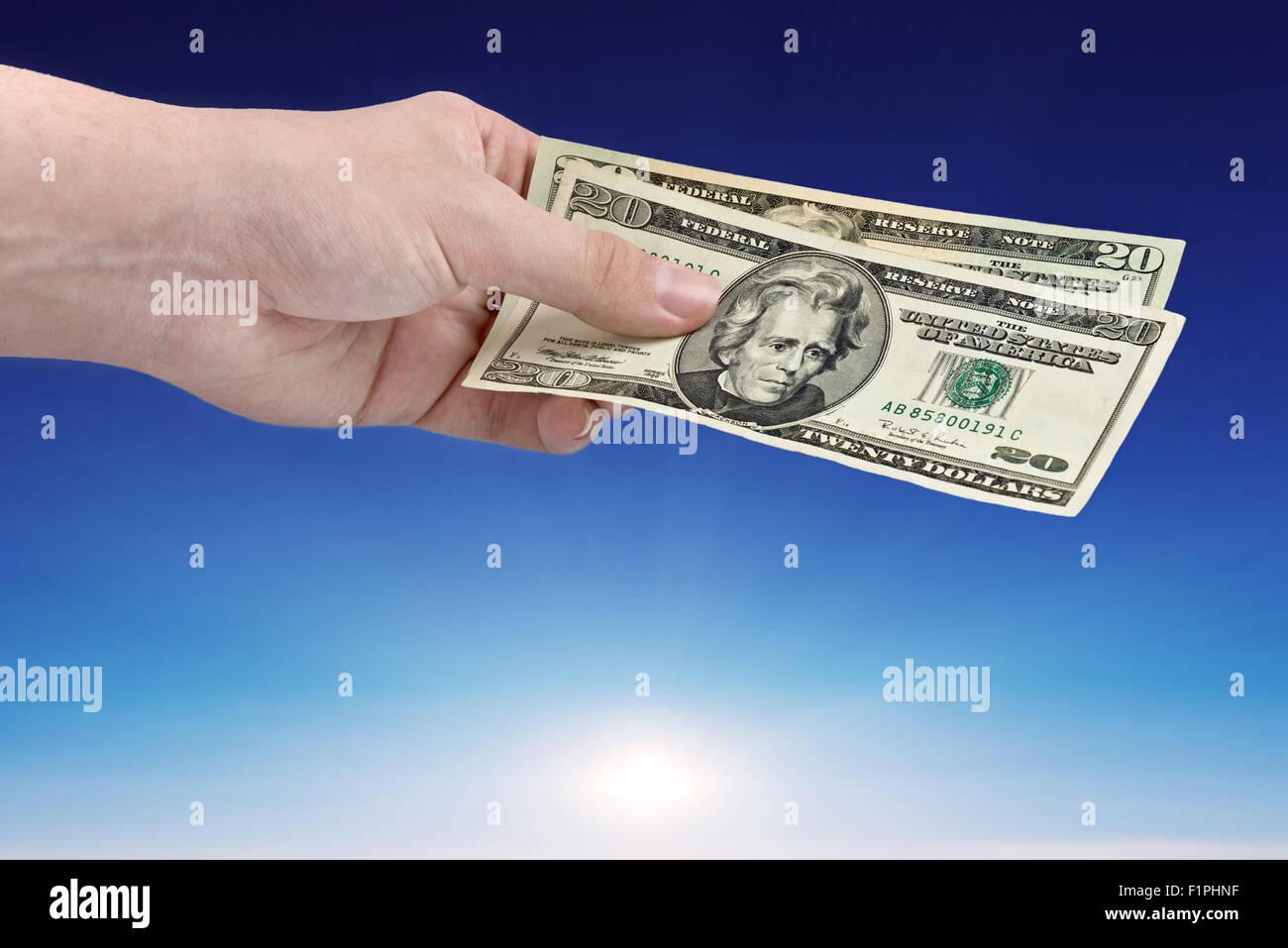 Men hand offer money over blue sky - Stock Image
