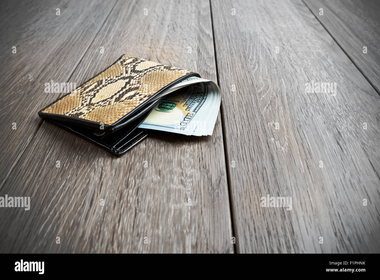 snake leather wallet with money on wooden background Stock Photo