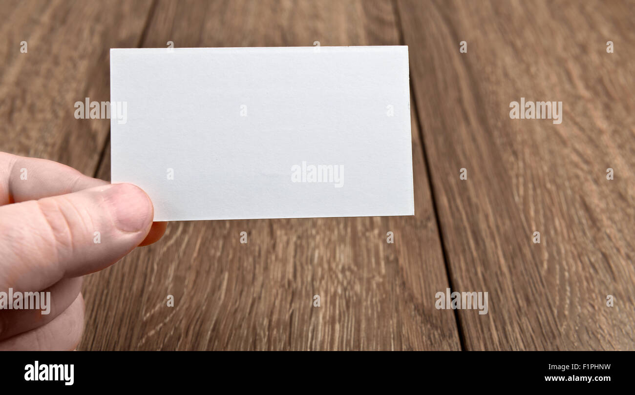 Business card in hand over wooden table Stock Photo