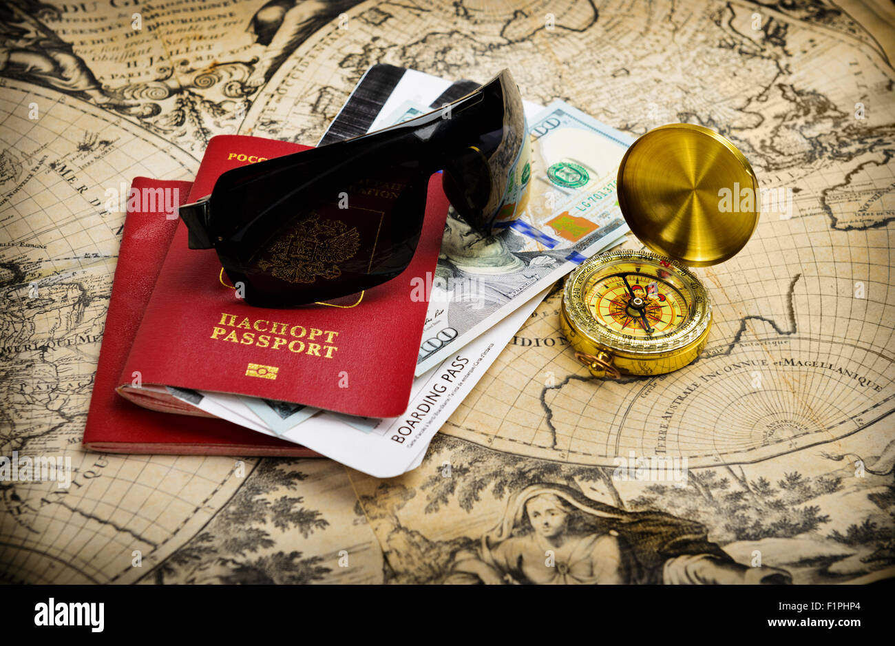 World travel concept. Passport and journey items on vintage world map - Stock Image
