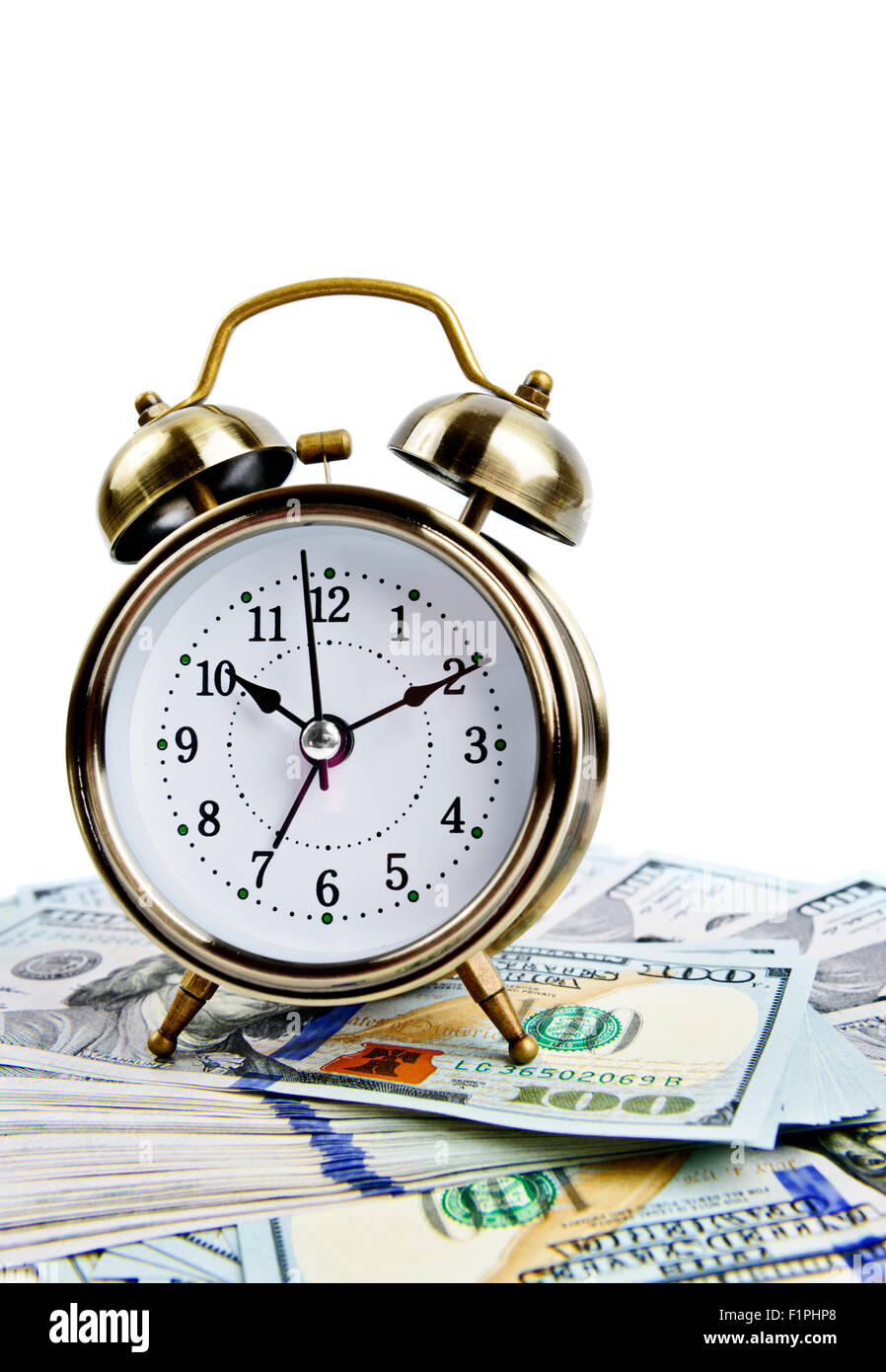 Vintage alarm clock over money - Stock Image