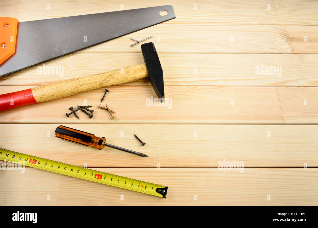 Saw, screw, tape measure and hammer on wood - Stock Image