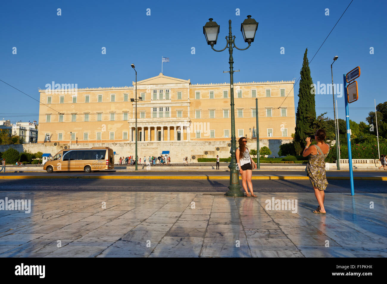 Tourists taking photos in front of the building of Greek parliament - Stock Image