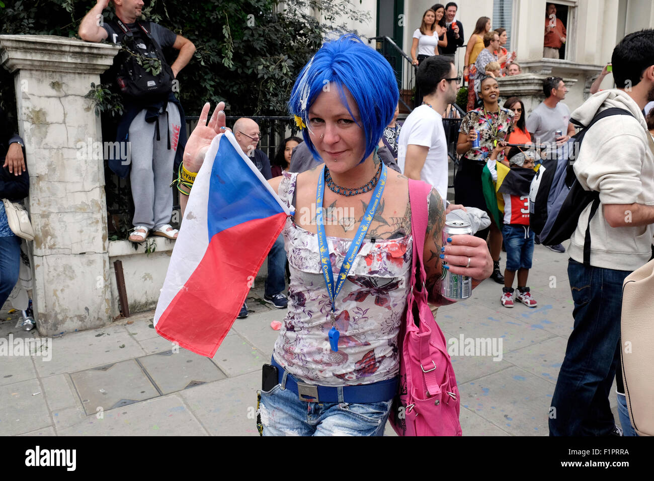 A woman with blue hair holds a Russian flag at Notting Hill carnival - Stock Image