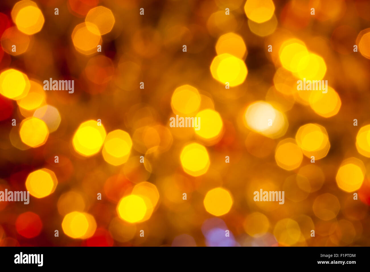 abstract blurred background - dark brown yellow and red shimmering Christmas lights bokeh of electric garlands on - Stock Image