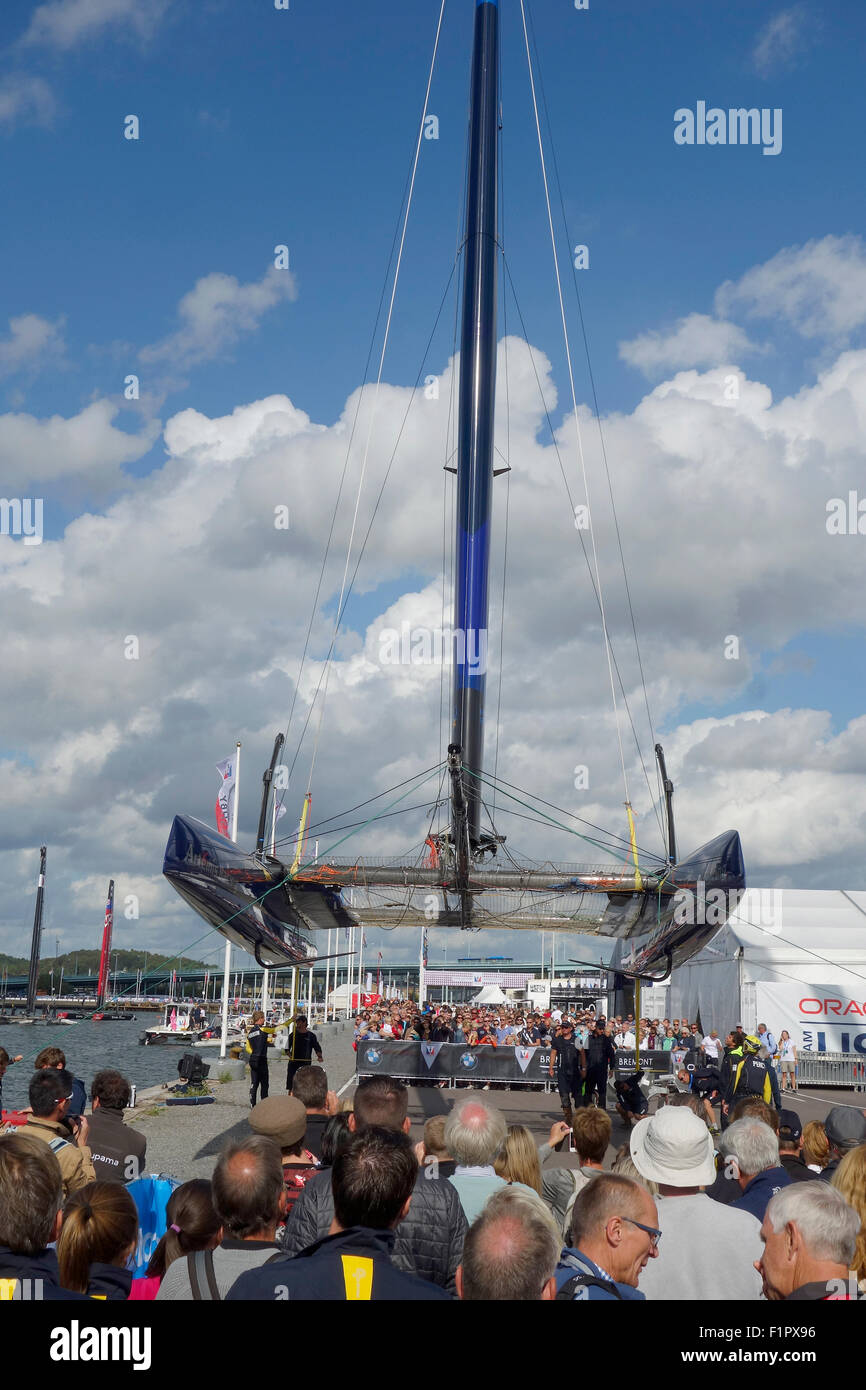 People gather and take opportunity to see Swedish America's Cup  72 class catamaran from below when it is lifted - Stock Image
