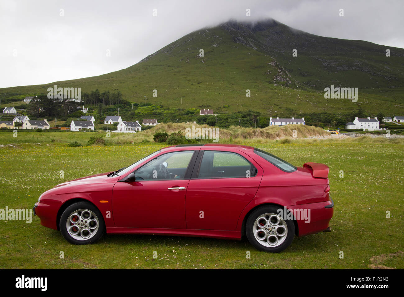 alfa 156 car parked on grass at doogort with view of slievemore Achill Island County Mayo Ireland - Stock Image
