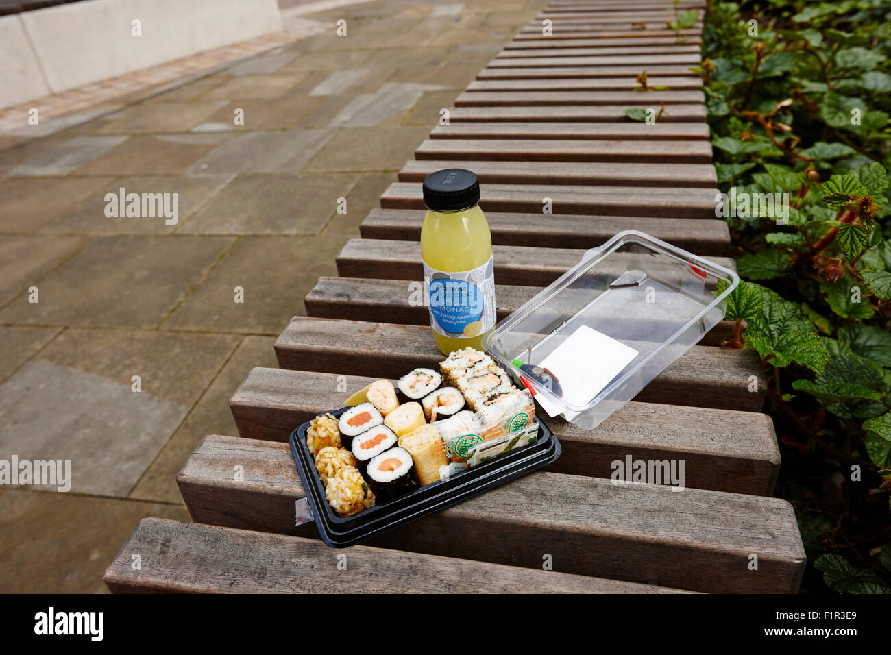 supermarket bought sushi and drink on a park bench Birmingham UK - Stock Image
